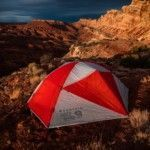 red-and-white-mountain-hard-wear-tent-on-ground-beside-rock-formation