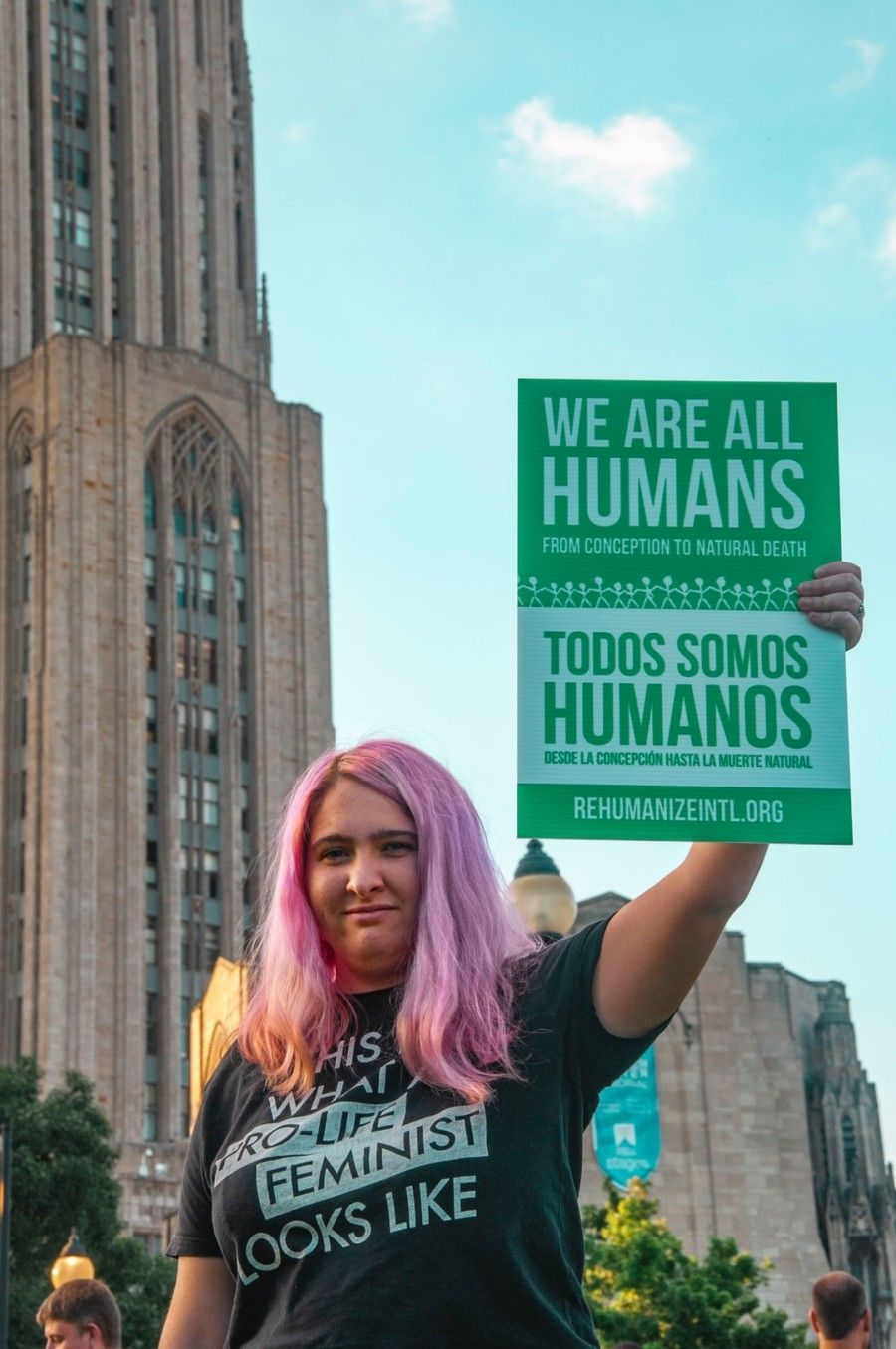 woman-with-pink-hair-holding-green-placard