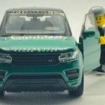 green-range-rover-suv-scale-model-with-minifig-standing-at-open-door