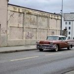 red-chevrolet-bel-air-parked-near-brown-building
