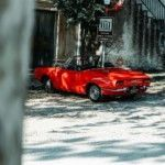 red-convertible-coupe-parked-beside-building