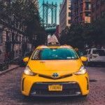 yellow-toyota-taxi-cab-parked-near-building
